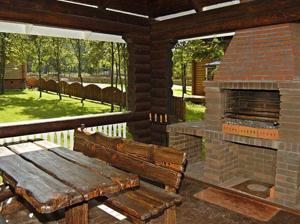 Деревянная мебель и печь внутри беседки