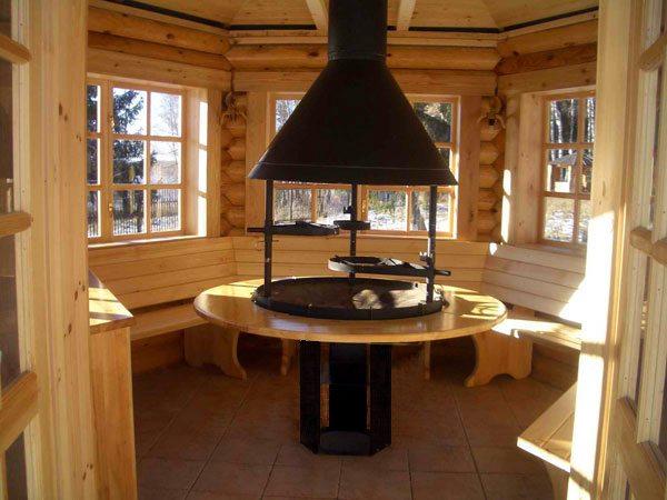 Фото барбекю, установленного внутри деревянной конструкции.
