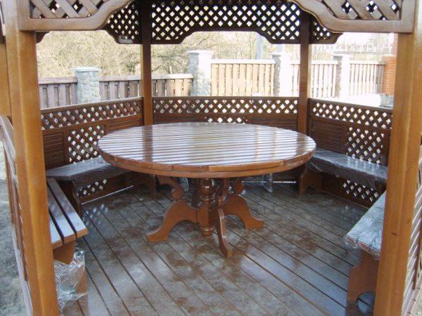 Фото многоугольной конструкции со стационарными деревянными скамейками и переносным столом.
