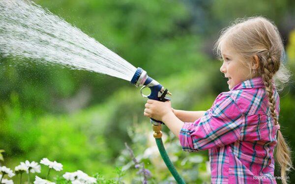 Ребенок поливает участок на даче из поливочного шланга