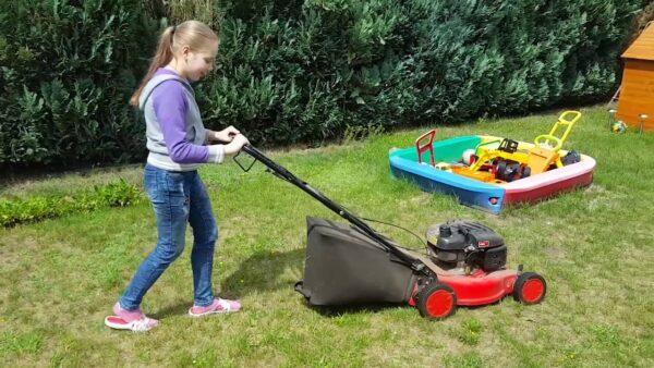 Ребенок помогает косить траву на даче