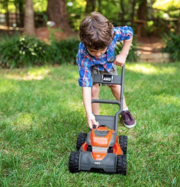 Ребенок с игрушечной газонокосилкой на даче