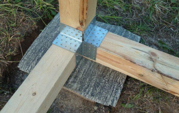 Закрепляем пол и опоры с помощью металлических уголков.