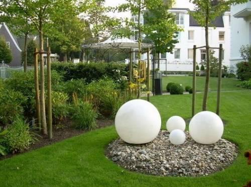 Каменная клумба, белые стеклянные фонари и металлическая фигурная беседка выглядят стильно и оригинально