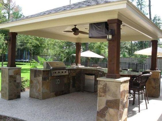 Классический навес на опорах, стилизованных под камень и дерево, приспособлен для эксплуатации в качестве открытой летней кухни