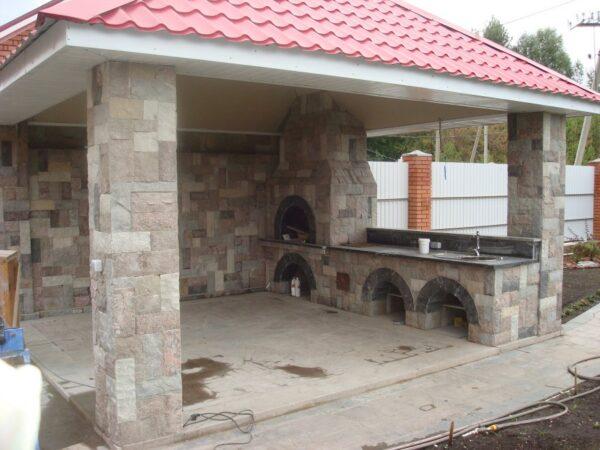 Красивым и практичным дополнением к каменной беседке станет каменный кухонный комплекс с камином.
