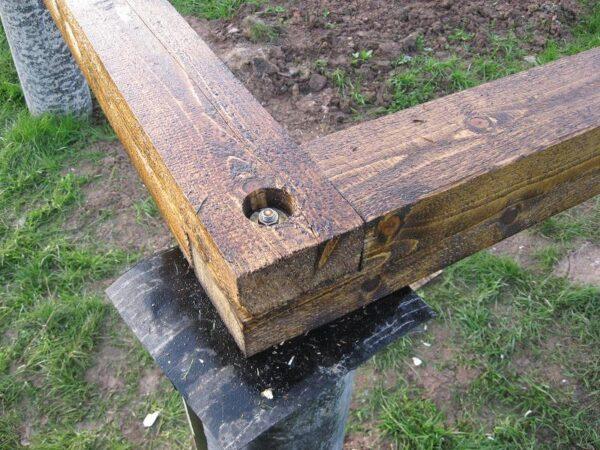 Между деревянным каркасом и бетонной сваей укладывается 2 слоя рубероида.