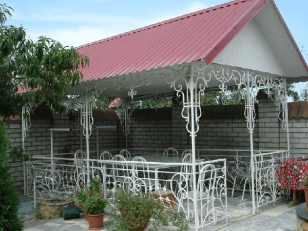 На фото – кованая беседка с двускатной крышей из профнастила