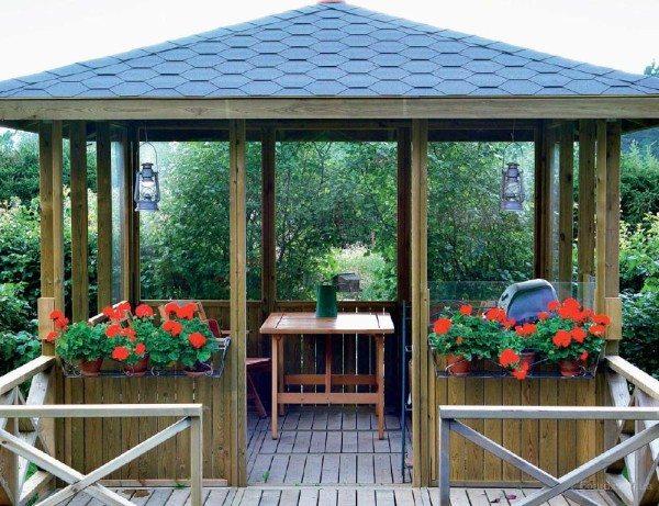 На фото деревянная беседка в саду.