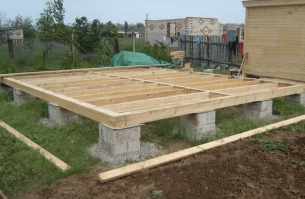 На фото изображен столбчатый фундамент из блоков с обвязкой из бруса.