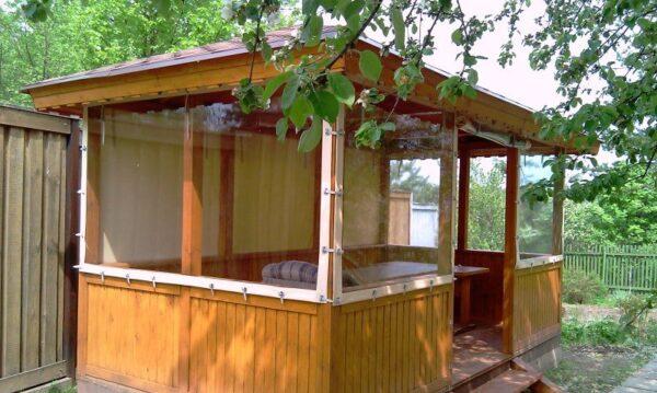 На фото показана деревянная беседка со шторами, которые изготовлены из прозрачного ПВХ.