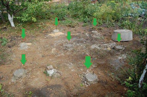 На фото показаны монолитные круглые столбики фундамента
