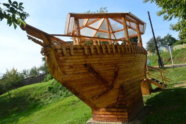 Плывущий по зелёному морю деревянный кораблик украсит собой любой садовый участок