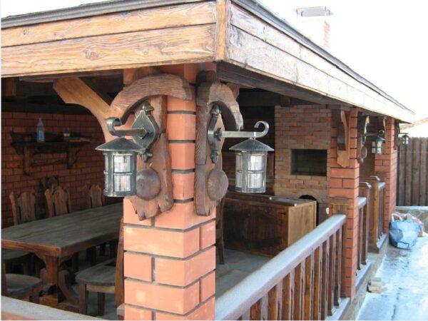 Пример открытой кухни, где кирпичные опоры сочетаются с деревянным заполнением проемов
