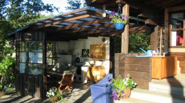 С домом из бруса или оцилиндрованного бревна лучше всего будет гармонировать деревянная постройка.