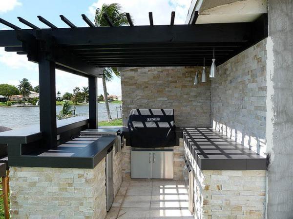Стильная пристроенная к дому пергола минималистично окрашена в черный цвет, что выгодно контрастирует с каменной стеной и оборудованием для барбекю