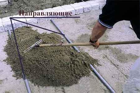Выравнивание песка по самодельным направляющим из труб