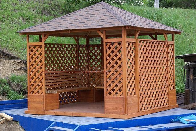 Закрытая деревянная беседка с решетчатыми стенками.