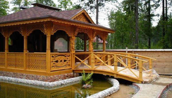На фото изображена беседка, украшенная мини прудом, мостиком и дорожкой.