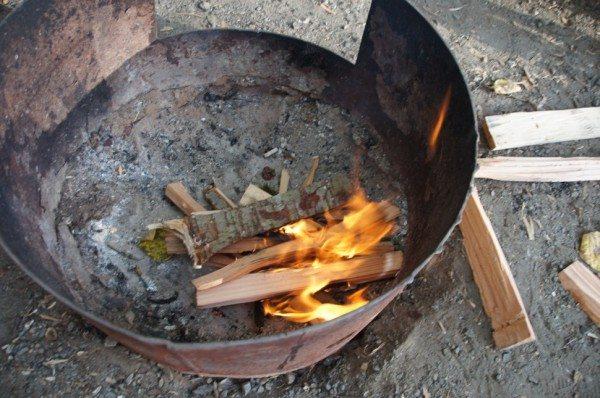 Обрезанная бочка с отверстием для закладки дров
